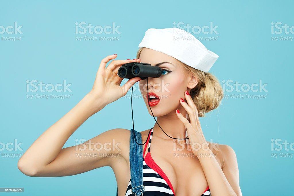 Pin-up style sailor woman looking through binoculars  20-24 Years Stock Photo