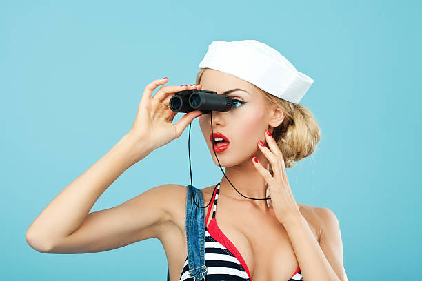 pin-up-stil matrose frau blick durch das fernglas - seemann thema stock-fotos und bilder