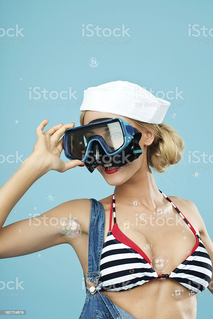 Pin-up style sailor woman looking through scuba mask Young Blond Woman Wearing Striped Bikini and Blue Overalls looking through scuba mask. Standing against blue background. Pin-Up style. Summer portrait. 20-24 Years Stock Photo