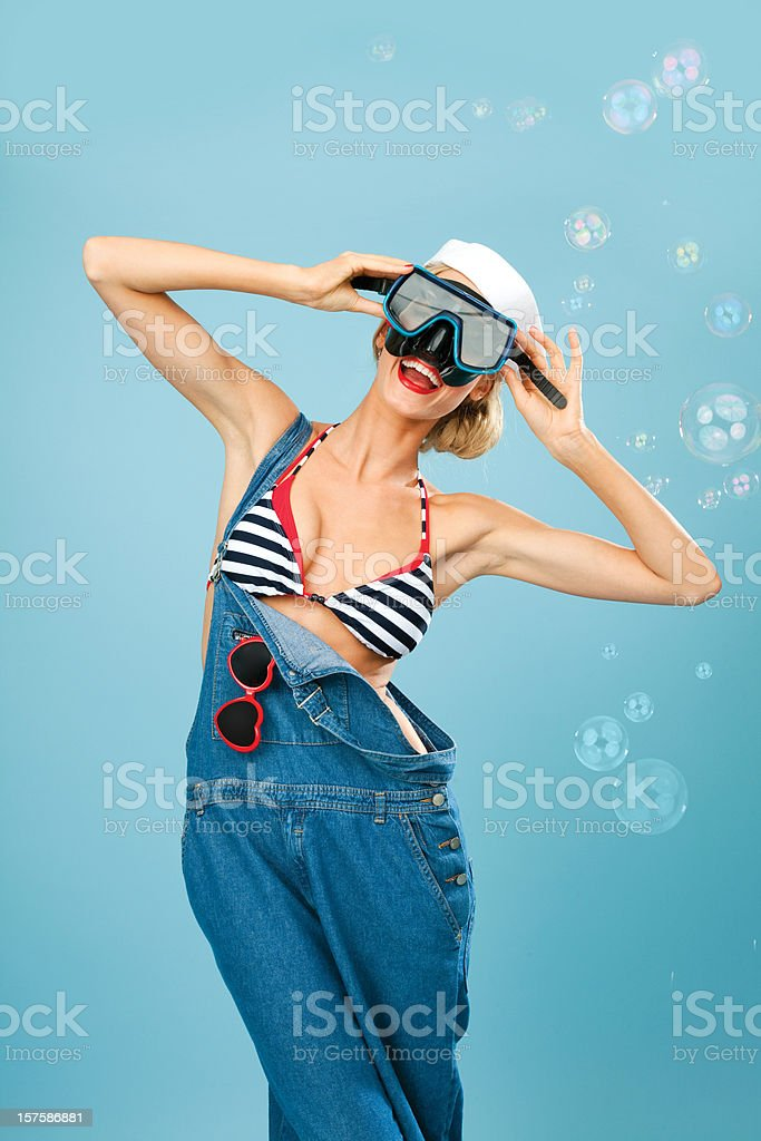 Pin-Up Style sailor woman posing with scuba mask Young Blond Woman Wearing Striped Bikini, Blue Overalls and Scuba Mask. Standing against blue background. Pin-Up style. Summer portrait. 20-24 Years Stock Photo