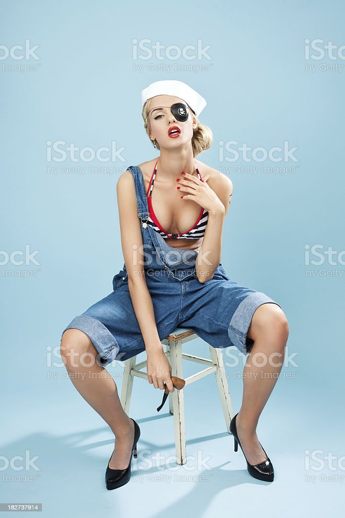 Pin-up style sailor woman with pipe and pirate eye patch Young Blond Woman Wearing Striped Bikini and Blue Overalls with pirate eye patch holding pipe in hand. Sitting on stool against blue background. Pin-Up style. Summer portrait. 20-24 Years Stock Photo