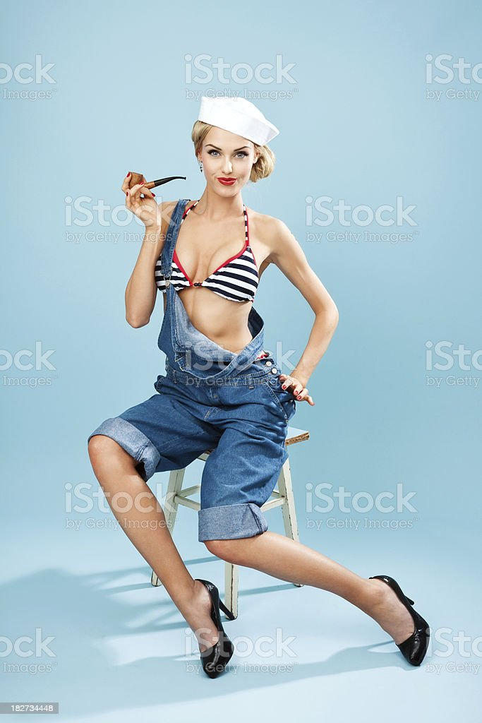 Pin-up style sailor woman with pipe Young Blond Woman Wearing Striped Bikini and Blue Overalls holding pipe in hand. Sitting on stool against blue background. Pin-Up style. Summer portrait. 20-24 Years Stock Photo