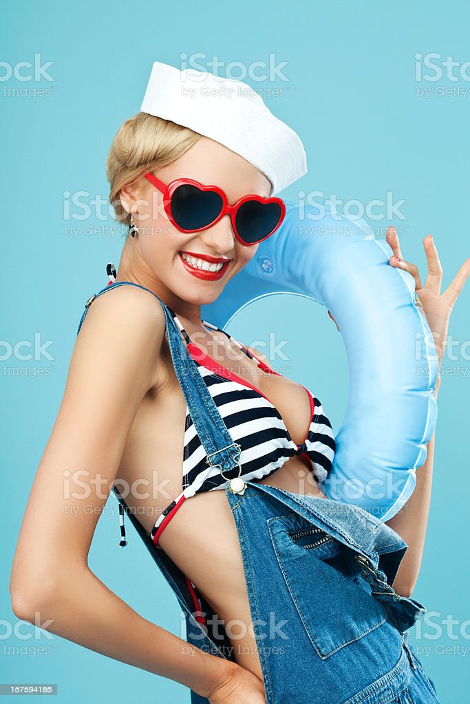 Pin-up style sailor woman with sunglasses and lifebouy Young Blond Woman Wearing Striped Bikini, Blue Overalls, sunglasses and holding blue lifebouy on arms. Standing against blue background. Pin-Up style. Summer portrait. 20-24 Years Stock Photo