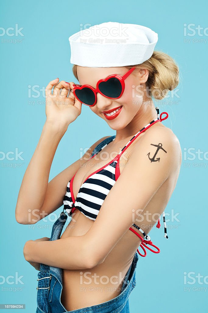 Pin-up style sailor woman with sunglasses Young Blond Woman with anchor tatoo on her arms Wearing Striped Bikini, Blue Overalls and sunglasses. Standing against blue background. Pin-Up style. Summer portrait. 20-24 Years Stock Photo
