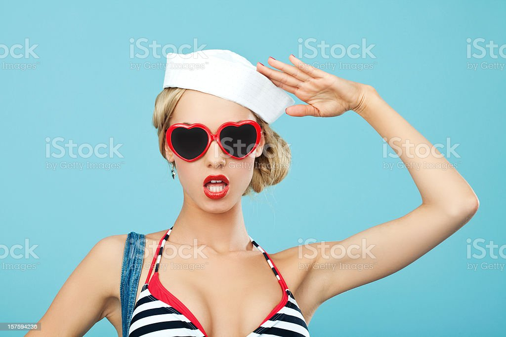 Pin-up style sailor woman with sunglasses saluting Young Blond Woman with anchor tatoo on her arms Wearing Striped Bikini and Blue Overalls Saluting. Standing against blue background. Pin-Up style. Summer portrait. 20-24 Years Stock Photo