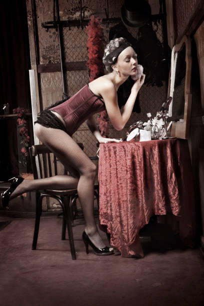pin-up style woman with curlers powdering face in mirror - burlesque stock photos and pictures