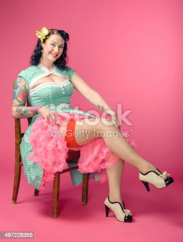 Attractive adult pin-up woman wearing 50s style dress, pink background