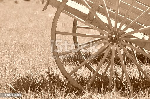 A pioneer handcart wooden wheel on a handcart sitting in a field of weeds, monochrome.