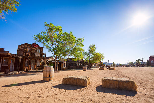 pioneer town buildings and hay stack on the street - western town stock photos and pictures