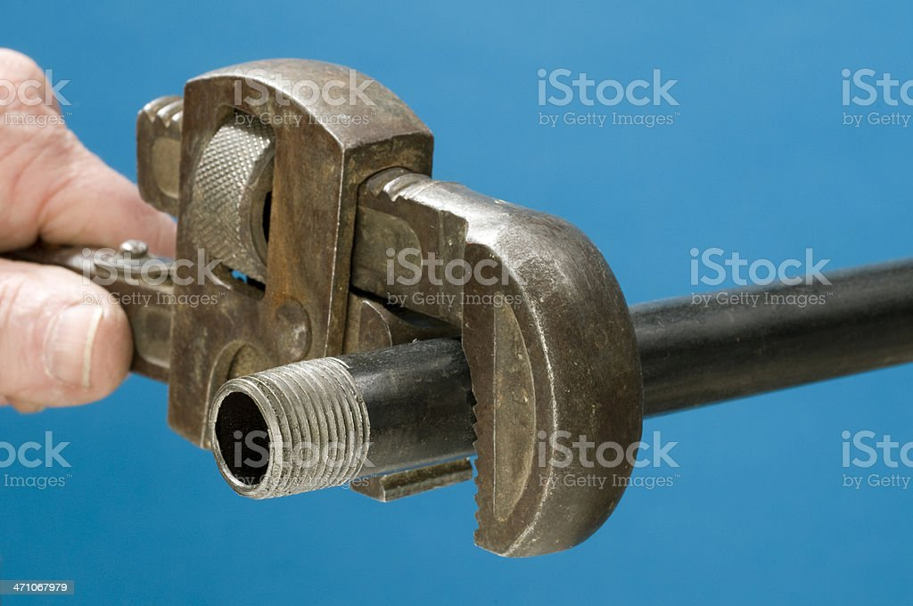 Pipe and adjustable wrench on blue background royalty-free stock photo