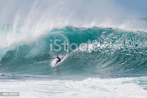 A surfer lines up a very large wave at the infamous Banzai Pipeline on the North Shore of Oahu