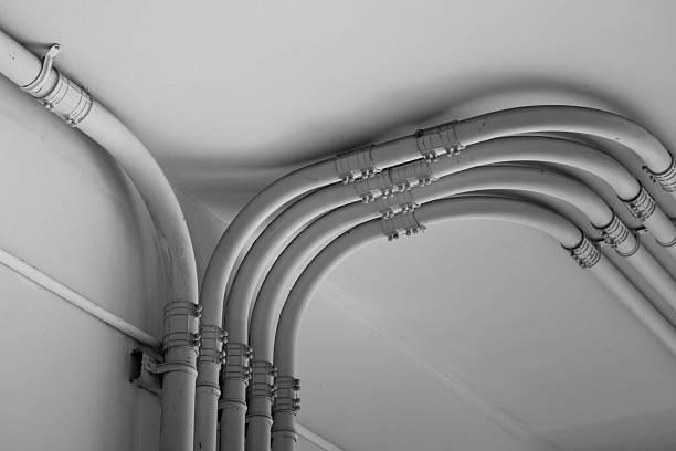 pipe strom linie auf zement-wand - kabelkanal weiß stock-fotos und bilder