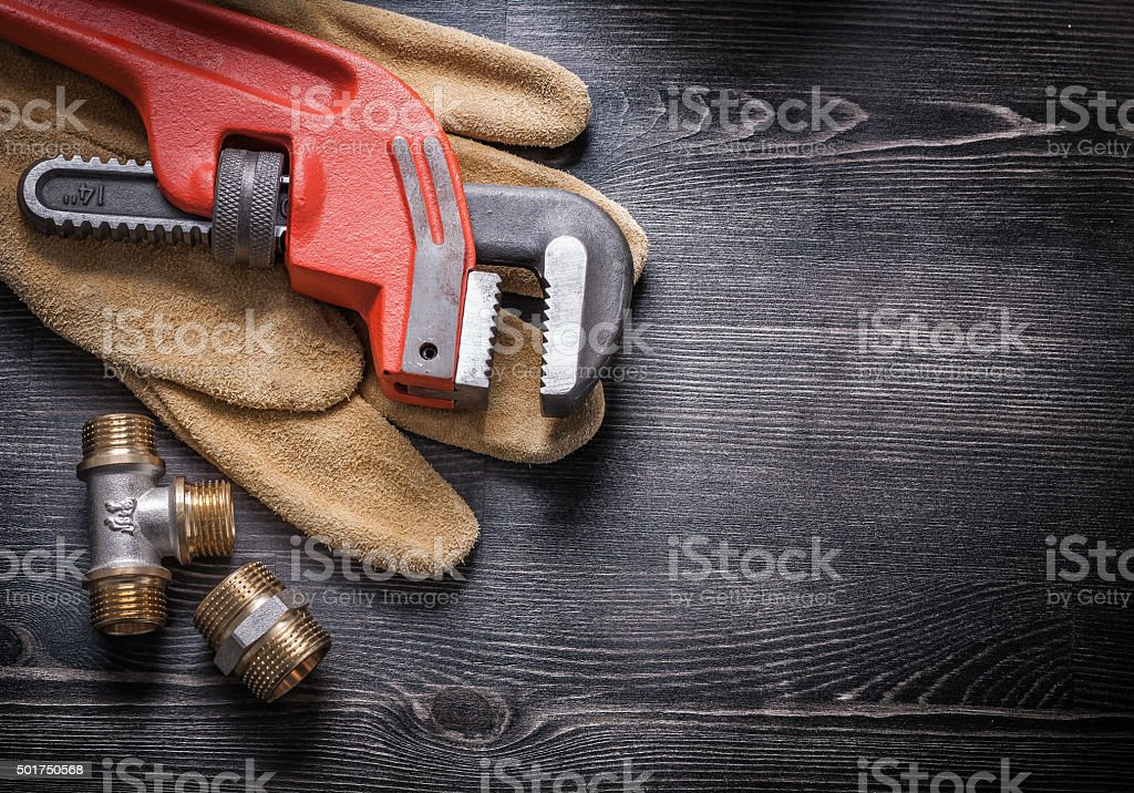Pipe wrench copper plumbing fixtures leather working gloves cons stock photo