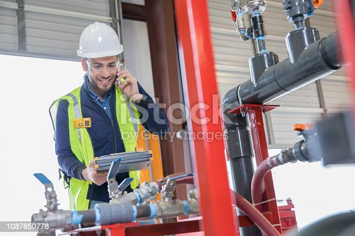 Young adult Hispanic man is an engineer working in oil and gas industry. He is inspecting pipeline equipment and making a phone call. Man is wearing hard hat and safety vest.