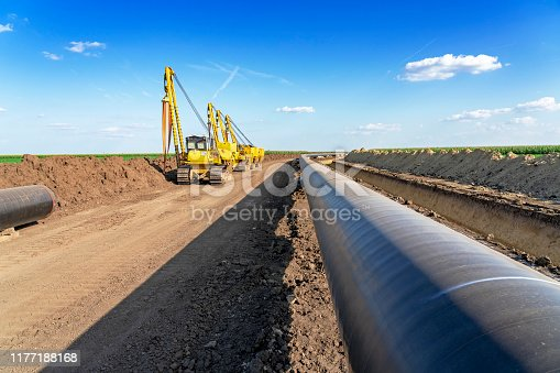 Heavy Machinery and Gas Pipeline Construction Site. Pipes are Laid on Top of Supportive Sandbags Beside Trench and Welded Together.