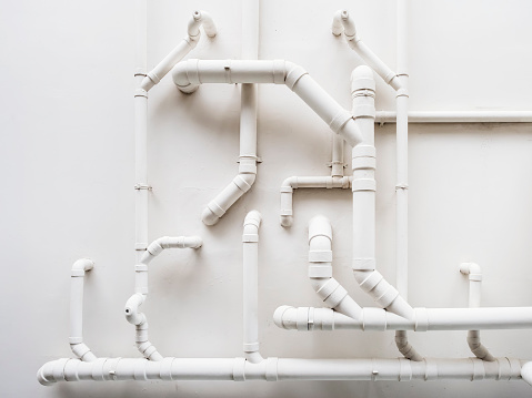 Pipeline Plumbing system on white wall Industrial object