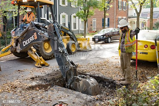 istock Pipeline Worker Directing Backhoe 617886770