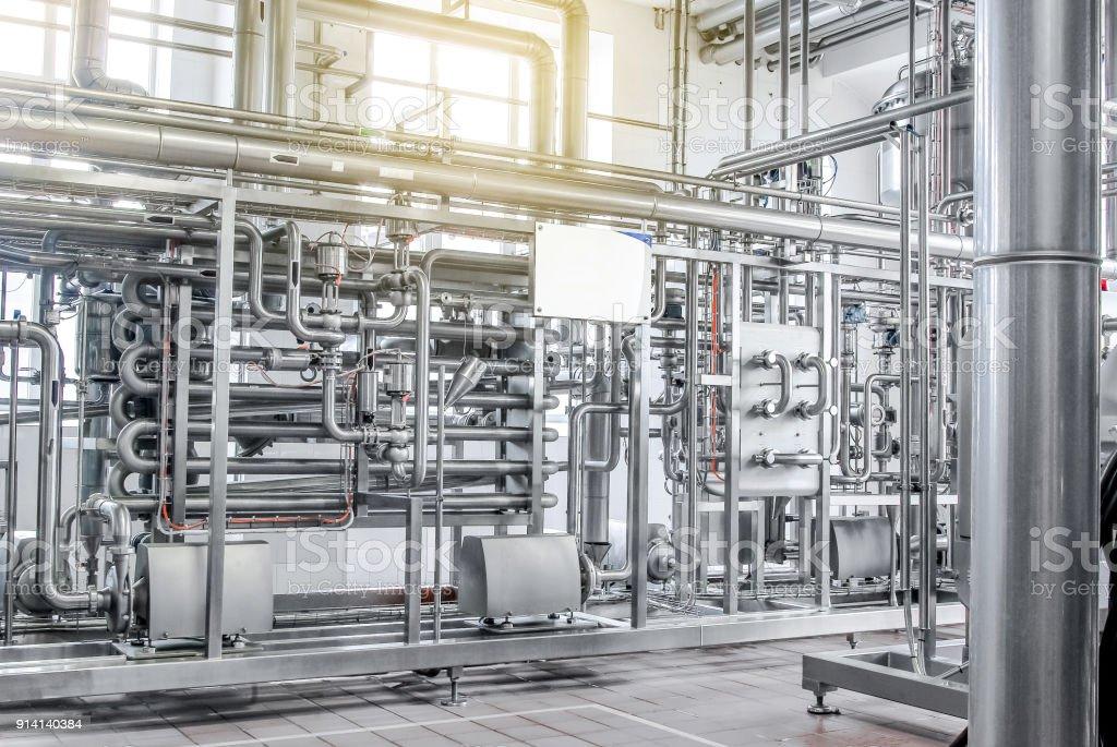 Rohrleitungen aus Edelstahl, ein System für pumpende Flüssigkeiten oder Milch für die Lebensmittelindustrie. Abstrakte Industrieerfahrung. – Foto