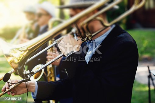 Musicians playing wind instruments. Young musicians are playing on trombones.
