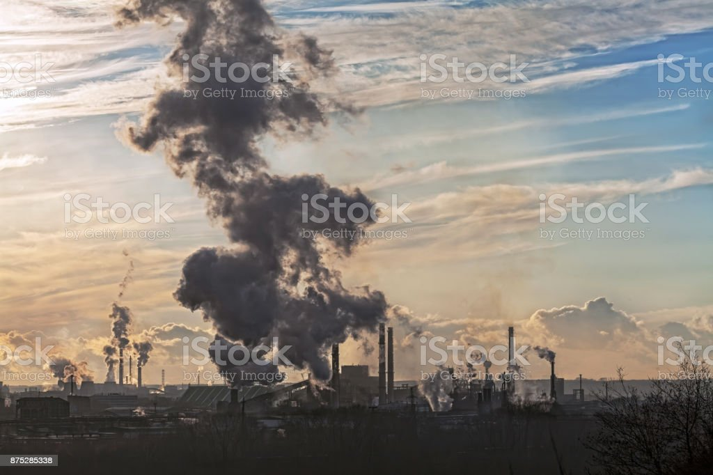pipes of a large plant smoke in the sky stock photo