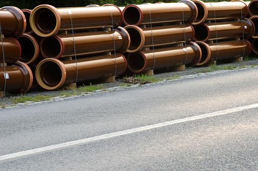 Stacks of pipes next to asphalt road.