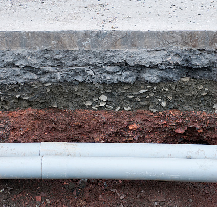 A pair of modern plastic pipes newly installed under the road surface.
