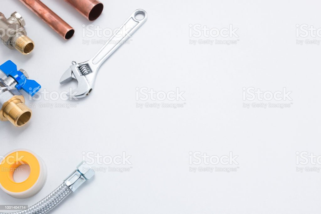 Pipes, Valves, Tape, and Spanner on White Background with Copy Space stock photo