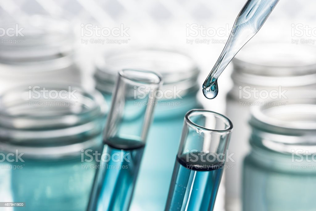 Pipette adding blue fluid test tube close up. stock photo