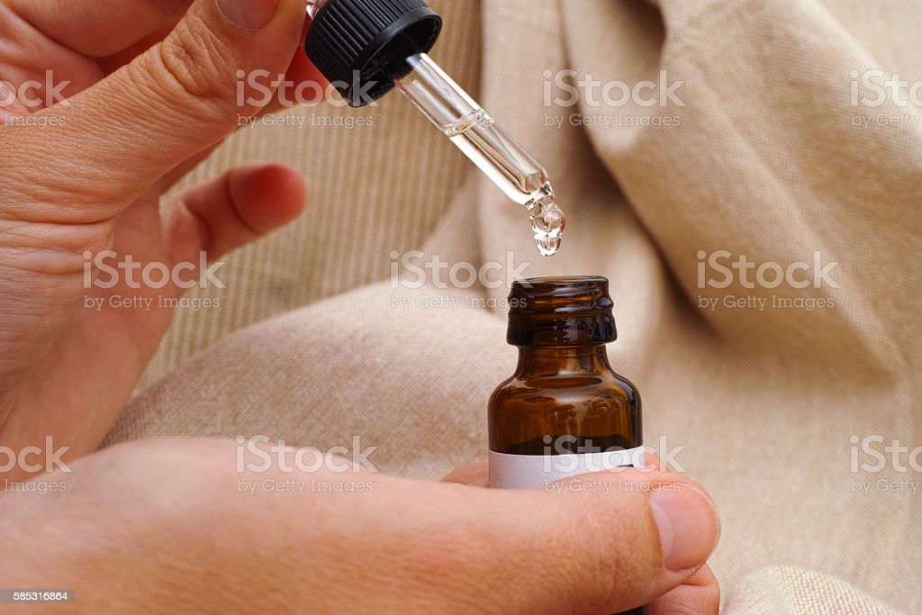 Pipette and oil bottle in woman hands stock photo
