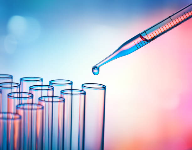 pipette dropping a sample into a test tube - closeup - laboratory stock photos and pictures