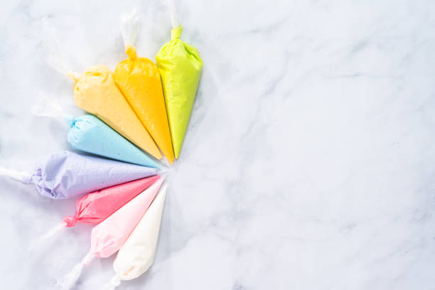 Piping bags with pastel color royal icing to decorate Easter sugar cookies Flat lay. Piping bags with pastel color royal icing to decorate Easter sugar cookies. icing bag stock pictures, royalty-free photos & images