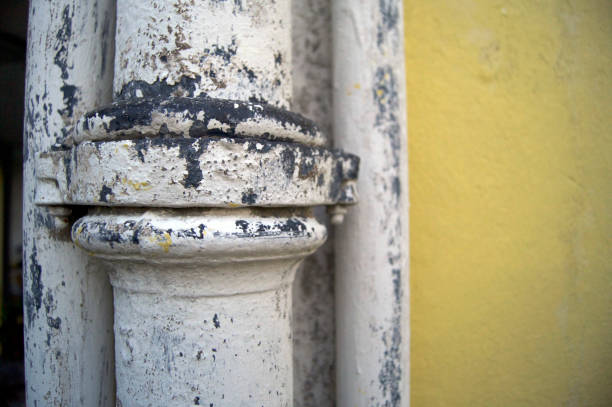 piping metal against a cemented wall stock photo