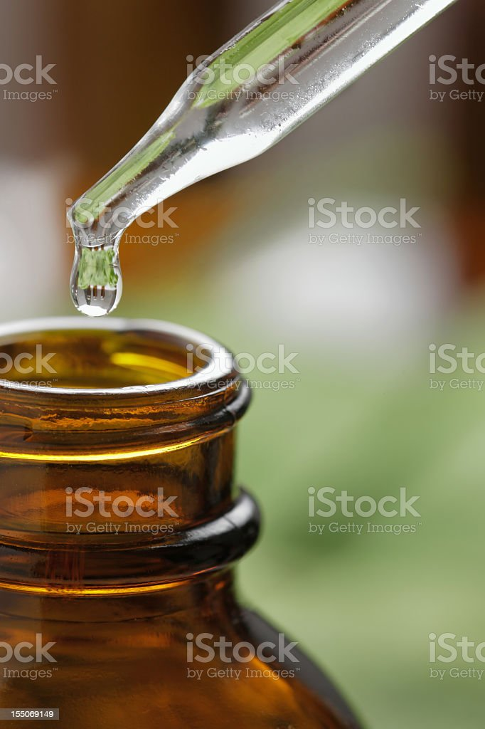 Pippete tip dispensing a drop of liquid in a bottle royalty-free stock photo