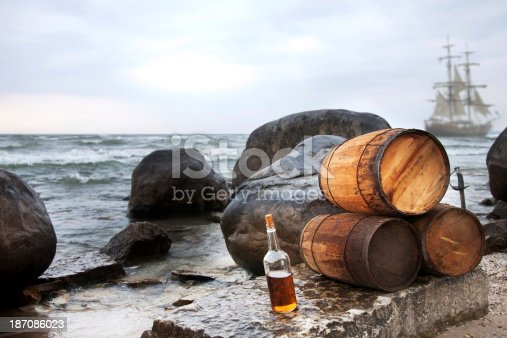 A pirate themed background with rum barrels, a sword, and an authentic tall ship.