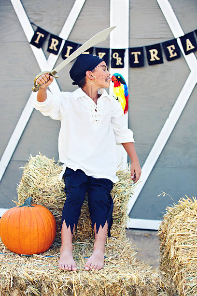 pirate boy kissing parrot at halloween party - swashbuckler stock photos and pictures