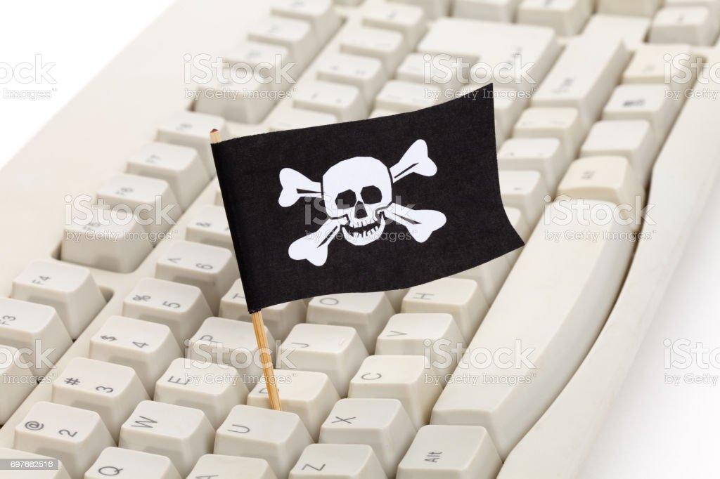 Bandera pirata y teclado de ordenador - foto de stock