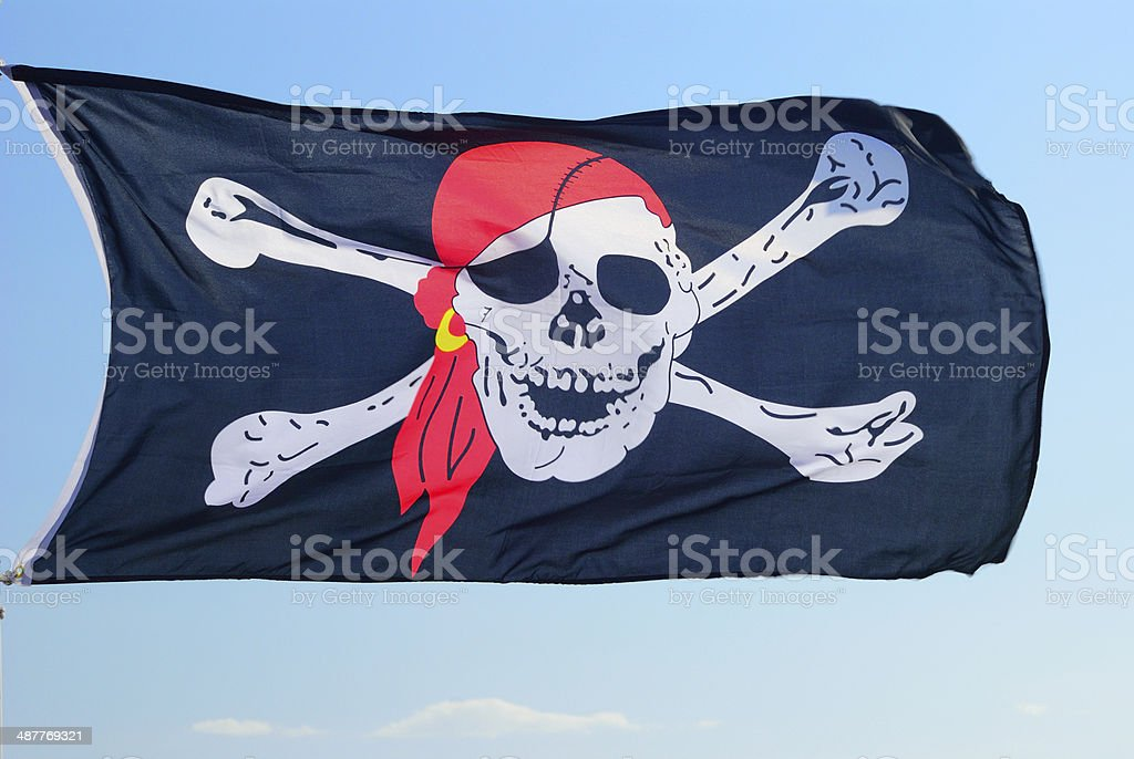 Pirate flag fluttering ominously on the wind stock photo