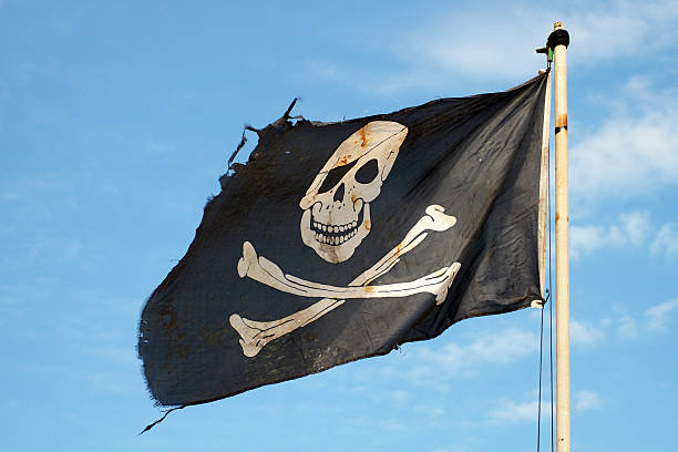 pirate flag in the wind against a blue sky - swashbuckler stock photos and pictures