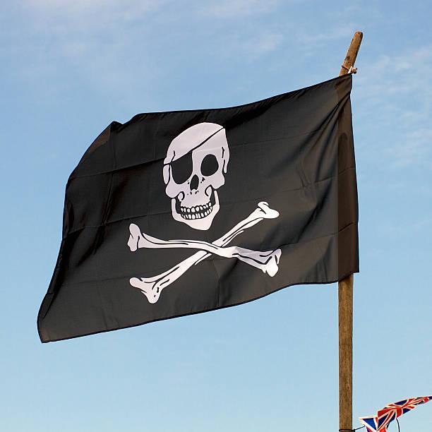 Bandera pirata en el viento en contra un cielo azul - foto de stock