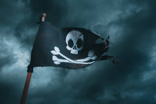 Pirate flag waving on smokey background Pirate flag waving with the wind on a smoky background pirate criminal stock pictures, royalty-free photos & images