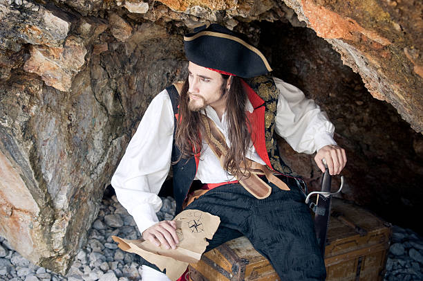 Pirate holding treasure map, sitting on a treasure chest stock photo