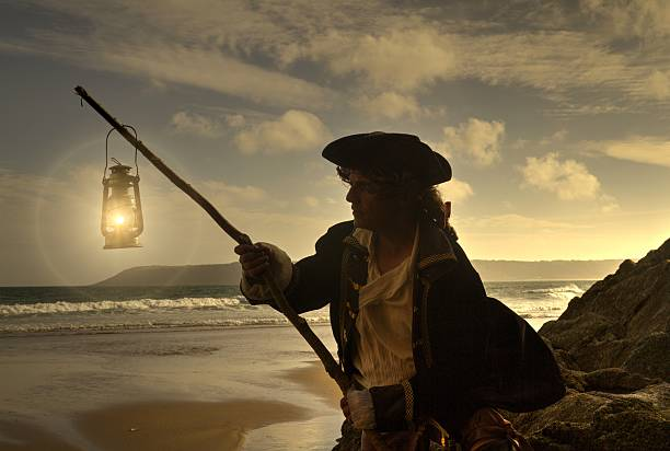 pirate on a beach with lantern at sunset - swashbuckler stock photos and pictures