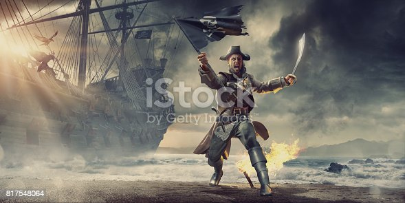 A conceptual image of male pirate on a beach behind a pirate ship on an stormy overcast evening. The pirate is holding a torn pirate flag and cutlass with mouth open shouting. He has a flaming torch in the sand behind him, and wears pirate clothes and has guns in holsters.