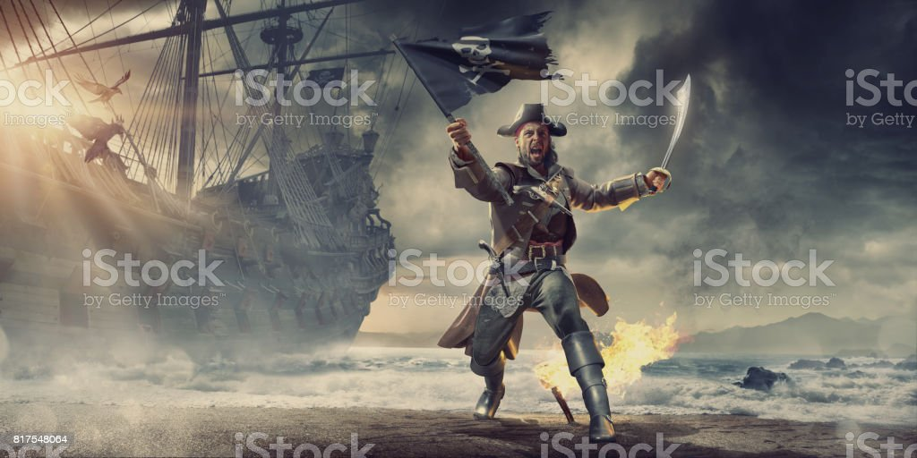 Pirate On Beach Holding Flag and Cutlass Near Pirate Ship stock photo
