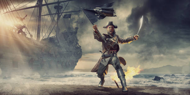 pirate on beach holding flag and cutlass near pirate ship - pirates stock photos and pictures
