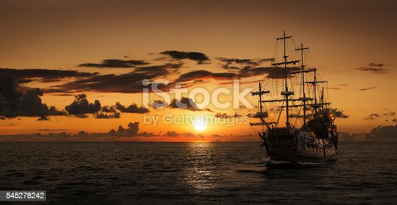 Silhouette of a pirate ship at the open sea with copy space