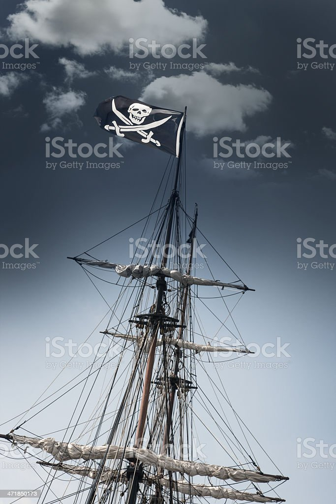 Pirate Ship with Jolly Roger Flag Leaning Under Dark Sky royalty-free stock photo