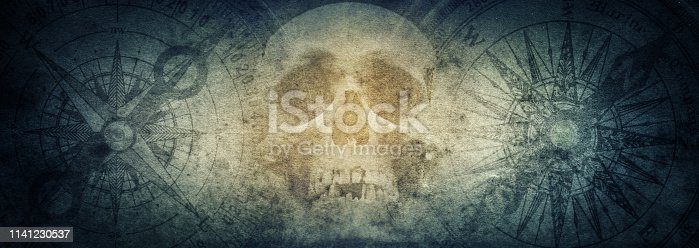 istock Pirate skull and compasses on old grunge paper background. 1141230537