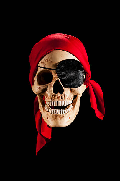 Pirate Skull wearing a red bandanna A Pirate skull wearing an eye patch and red bandanna against a black background costume eye patch stock pictures, royalty-free photos & images