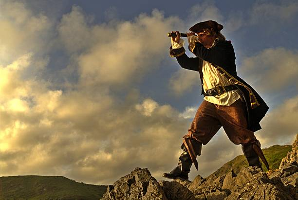 pirate standing on rocks looking through his telescope - swashbuckler stock photos and pictures